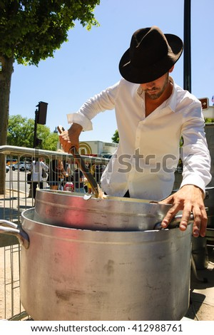 PARIS, FRANCE - JUNE 6, 2015: Young chef preparing Aligot (traditional dish from Aveyron area made from cheese blended into mashed potatoes) at food festival on Avenue des Champs-Elysees. - stock photo