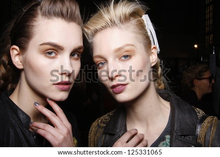 PARIS, FRANCE - MARCH 06: A  pair of models gets ready backstage at the Kenzo fashion show during Paris Fashion Week on March 6, 2011 in Paris, France. - stock photo