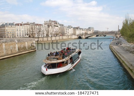 PARIS, FRANCE - MARCH 18, 2014: An excursion boat heads towards the Pont De La Tournelle on the River Seine. Numerous such boats ply the Seine each day, passing many famous Paris landmarks. - stock photo