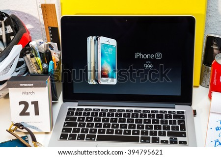 PARIS, FRANCE - MARCH 21, 2016: Apple Computers website on MacBook Pro Retina in a creative room environment showcasing Apple Event with Greg Joswiak presenting new iPhone se and 399 price - stock photo