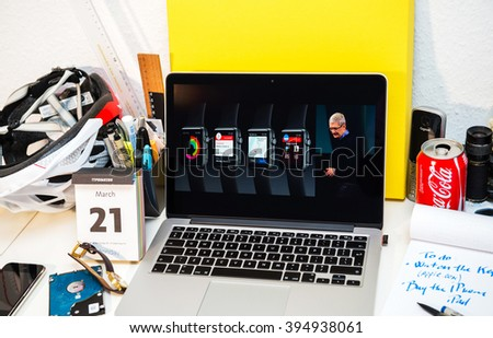 PARIS, FRANCE - MARCH 21, 2016: Apple Computers website on MacBook Pro Retina in a creative room environment showcasing Apple Event with Tim Cook and Apple watch faces - stock photo