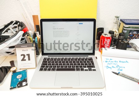 PARIS, FRANCE - MARCH 21, 2016: Apple Computers website on MacBook Pro Retina in a geek creative room environment showcasing the newly announced iPhone SE with Faster LTE and WI-FI - stock photo