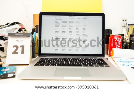 PARIS, FRANCE - MARCH 21, 2016: Apple Computers website on MacBook Pro Retina in a geek creative room environment showcasing the newly announced iPhone SE compared with other iPhone on power modes - stock photo
