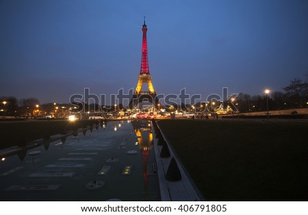 PARIS, FRANCE- MARCH 24, 2016: Eiffel tower illuminated with colors of the Belgian national flag to honor to victims of terrorist's attack in Brussels.