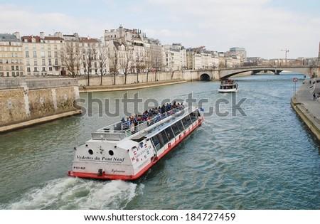 PARIS, FRANCE - MARCH 18, 2014: Excursion boats head towards the Pont De La Tournelle on the River Seine. Numerous such boats ply the Seine each day, passing many famous Paris landmarks. - stock photo