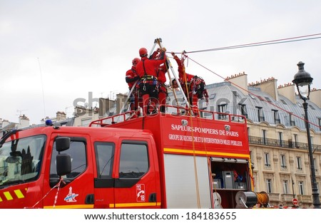 PARIS, FRANCE - MARCH 18, 2014: Firefighters of the elite GRIMP unit carry out a training exercise at the Pont Saint Michel on the River Seine. The unit specialises in rescues in hazardous situations. - stock photo