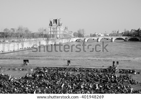 PARIS, FRANCE - MARCH 12, 2016: Love locks bridge in Paris and the view of the Louvre museum. Ritual of affixing padlocks, as symbol of love, is spread from 2000s. - stock photo