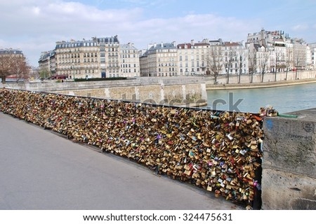 PARIS, FRANCE - MARCH 18, 2014: Padlocks on the Pont de L'Archeveche (Archbishops bridge) over the River Seine. Thousands of lovers attach them as a symbol of eternal love. - stock photo