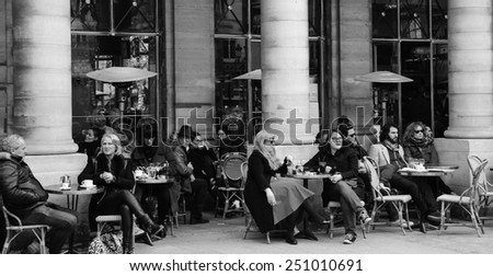 PARIS, FRANCE - MARCH 2, 2014: Parisians and tourists sit on the terrace of Le Nemours cafe. This popular cafe, ideal place for people watching, is located near Palais Royal and Comedie Francaise. - stock photo