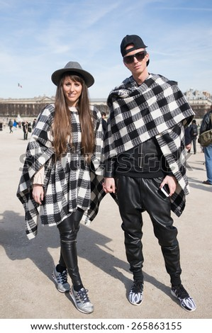PARIS, FRANCE - MARCH 7, 2015: Stylish couple with checkerboard scarf  in the Tuileries Garden. Paris Fashion Week: Ready to Wear 2015/2016 is held from March 3 to 11, 2015. - stock photo