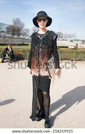 PARIS, FRANCE - MARCH 6, 2015: Stylish European woman with black skirt in the Tuileries Garden. Paris Fashion Week: Ready to Wear 2015/2016 is held from March 3 to 11, 2015. - stock photo