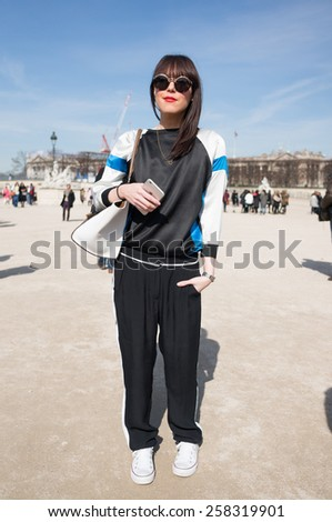 PARIS, FRANCE - MARCH 6, 2015: Stylish european woman with black sportswear in the Tuileries Garden. Paris Fashion Week: Ready to Wear 2015/2016 is held from March 3 to 11, 2015. - stock photo