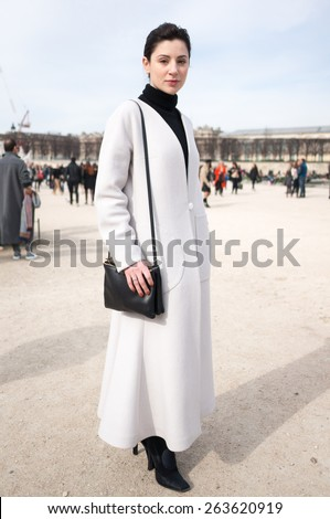 PARIS, FRANCE - MARCH 7, 2015: Stylish European woman with light gray robe in the Tuileries Garden. Paris Fashion Week: Ready to Wear 2015/2016 is held from March 3 to 11, 2015. - stock photo