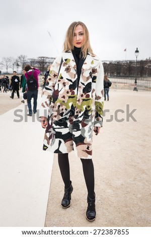 PARIS, FRANCE - MARCH 10, 2015: Stylish European woman with Military camouflage robe in the Tuileries Garden. Paris Fashion Week: Ready to Wear 2015/2016 is held from March 3 to 11, 2015. - stock photo