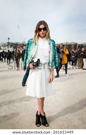 PARIS, FRANCE - MARCH 7, 2015: Stylish European woman with white skirt in the Tuileries Garden. Paris Fashion Week: Ready to Wear 2015/2016 is held from March 3 to 11, 2015. - stock photo
