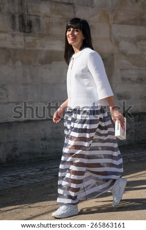 PARIS, FRANCE - MARCH 7, 2015: Stylish European woman with white strip skirt in the Tuileries Garden. Paris Fashion Week: Ready to Wear 2015/2016 is held from March 3 to 11, 2015. - stock photo