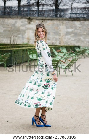 PARIS, FRANCE - MARCH 10, 2015: Stylish European woman withflower pattern skirtin the Tuileries Garden. Paris Fashion Week: Ready to Wear 2015/2016 is held from March 3 to 11, 2015. - stock photo