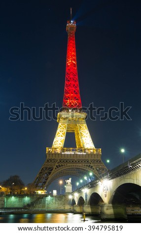 Paris; France-March 22, 2016 : The Eiffel tower lit up with the colors of National Belgian flag to honor to victims of terrorist's attack in Brussels. - stock photo