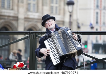 PARIS, FRANCE - MARCH 25, 2016: Unidentified senior musician play accordion on the Pont des Arts or Passerelle des Arts bridge across river Seine - stock photo