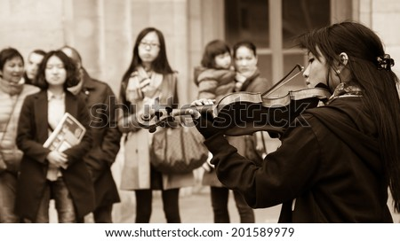 PARIS, FRANCE - MARCH 2, 2014: Violinist plays at Comedie Francaise square before audience consisting mainly of tourists . Dozens buskers perform on the streets and in metro of Paris.