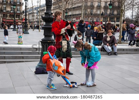 PARIS, FRANCE - MARCH 2, 2014: Young Scottish bagpiper in traditional costume plays music at  Place de la Republique before the public and the unidentified children put the money into his hat. - stock photo