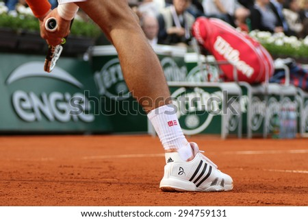 PARIS, FRANCE- MAY 28, 2015: Eight times Grand Slam champion Novak Djokovic wears custom Adidas tennis shoes during third round match at Roland Garros 2015 in Paris, France - stock photo