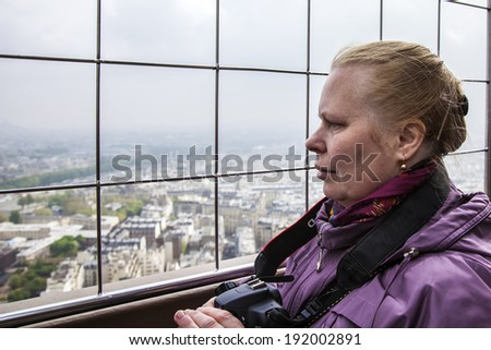 Paris, France, May 2, 2013 . Elderly tourist photographing the city from the observation platform of the Eiffel Tower