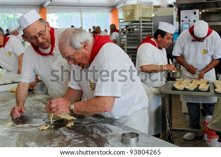 PARIS, FRANCE - MAY 16 - Fete du pain (Holiday of bread) near  Notre-Dame, unidentified bakers make pastries at bakery competition on May 16, 2010 in Paris - stock photo