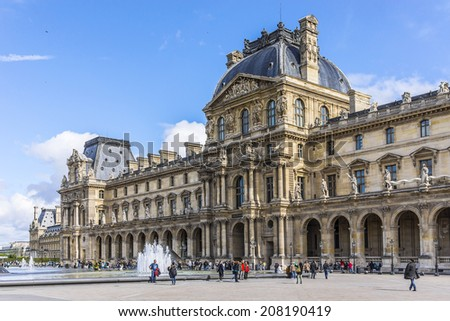 PARIS, FRANCE - MAY 8, 2014: Fountains and Glass pyramid in courtyard of Louvre Palace. Louvre Museum is one of the largest and most visited museums worldwide.