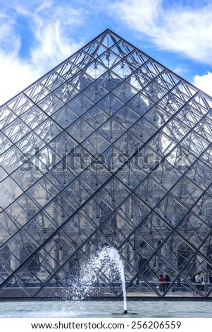 PARIS, FRANCE - MAY 8, 2014: Fountains and Glass pyramid in courtyard of Louvre Palace. Louvre Museum is one of the largest and most visited museums worldwide. - stock photo