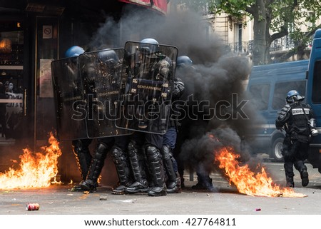 Paris, FRANCE - MAY 17, 2016 : French police, anti-riot squad,surrounded by fire during the massive protest over the labor law reforms. - stock photo