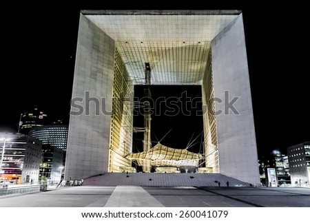 """PARIS, FRANCE - MAY 13, 2014: Grand Arch (""""Grande Arche de la Defense"""", 1989) at night - a monument in business district of Defense. Arch is a monument to humanity and humanitarian ideals. - stock photo"""