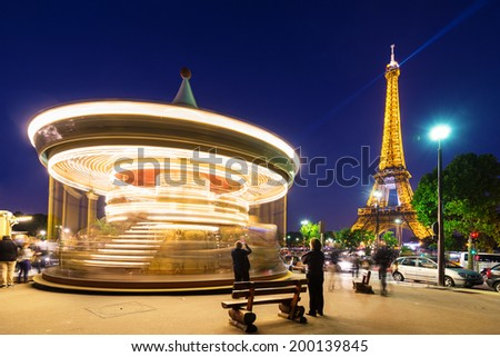 PARIS, FRANCE - MAY 17, 2014: Illuminated vintage carousel close to Eiffel Tower, Paris.