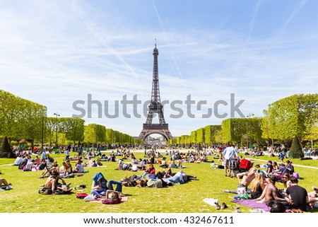 PARIS, FRANCE - MAY 5, 2016: Lots of people relaxing and having fun on Champ de Mars with the Eiffel Tower on background on a sunny day. - stock photo