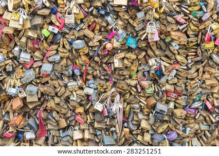 PARIS, FRANCE - MAY 29: Love padlocks representing eternal love of couples who lock padlocks at bridges over the Seine river on May 29, 2015 in Paris, France - stock photo