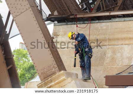 Paris, France - May 9, 2014: Man steeplejack washes foundation of the Eiffel Tower.