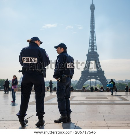 PARIS, FRANCE - MAY 14, 2014: National Police in front of the Eiffel Tower. The National Police comes under the jurisdiction of the Ministry of the Interior and has about 150,000 employees. - stock photo