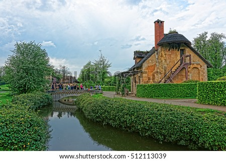 Paris, France - May 5, 2012: Old village of Marie Antoinette and the Palace of Versailles in Paris in France. People on the background