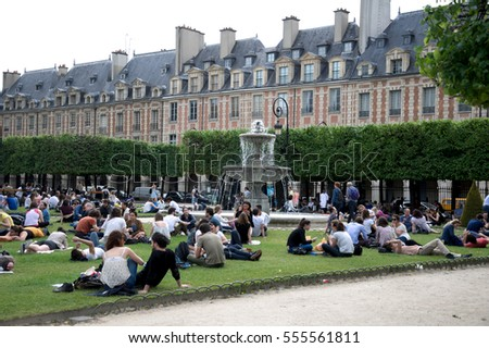 PARIS, FRANCE - MAY 2016 : Parisian relaxing in Place des Voges garden on May 21, 2016 in Paris, France