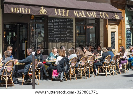 PARIS, FRANCE - MAY 15, 2014: People having lunch outdoors sit on a typical bistro on the street. - stock photo