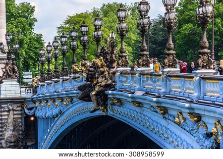 PARIS, FRANCE - MAY 14, 2014: Pont Alexandre III (1896) bridge spanning river Seine, connecting Champs-Elysees quarter and Invalides. It is most extravagant bridge and historical monument. - stock photo