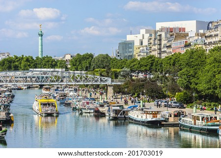 PARIS, FRANCE - MAY 18, 2014: Row of houseboats docked on Canal Saint Martin - a 4,5 km long canal; it connects canal de l'Ourcq to river Seine. - stock photo