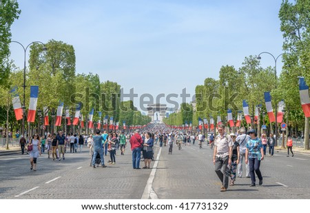 Paris, France - May 8, 2016. The famous Avenue des Champs Elysees in the heart of Paris, with a view towards the Arc de Triomphe. Local authorities closed the main road for vehicles on that Sunday. - stock photo