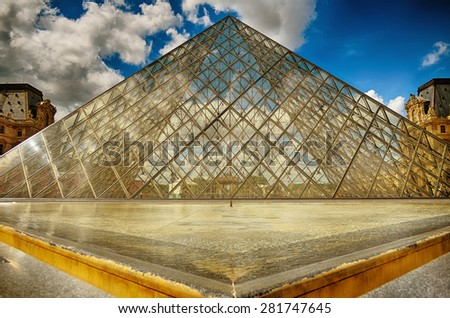 PARIS, FRANCE- MAY 5, 2015: The large glass pyramid and the main courtyard of the Louvre Museum on May 5, 2015. The Louvre Museum is one of the largest museums of the world - stock photo
