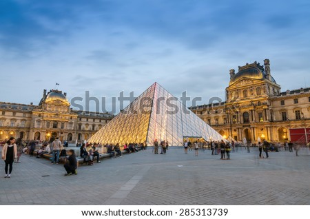 Paris, France - May 14, 2015: Tourist visit Louvre museum at dusk on May 14, 2015 in Paris. This is one of the most popular tourist destinations in France. - stock photo