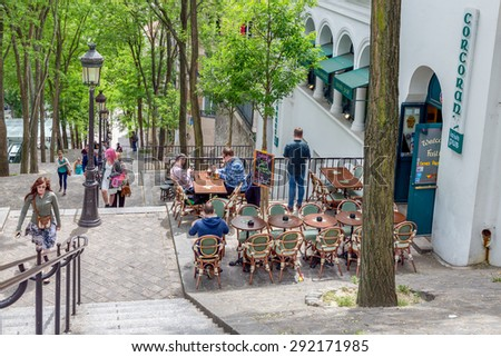 PARIS, FRANCE - May 28:  Tourists climbing the stairs with an Irish pub near Montmartre, one of the most touristic attractions of the city, on May 28, 2015, Paris, France - stock photo