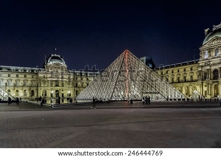 PARIS, FRANCE - MAY 15, 2014: View of illuminated buildings and pyramid in the courtyard of the Louvre Museum at night. The Louvre is one of the world's largest museums.