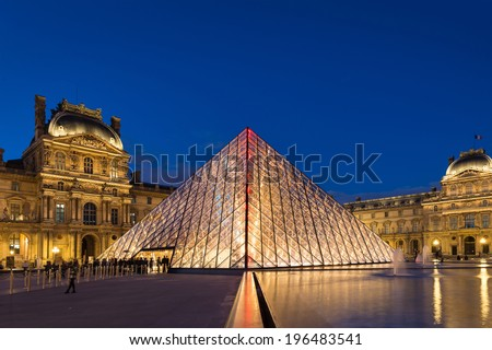 PARIS, FRANCE - MAY 13, 2014: View of the Louvre Museum and the Pyramid at twilight. The Louvre is the most famous and visited Museum in Paris, it display over 60,000 sq.M. of exhibition space.