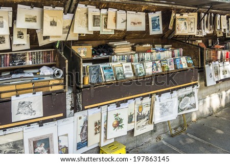 PARIS, FRANCE - MAY 18, 2014: Vintage books and pictures in open book market on embankment of river Seine near cathedral Notre Dame de. Book market on the banks of Seine is there since 16th century.