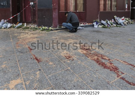 """PARIS, FRANCE - NOVEMBER 14, 2015 :  A man lights a candle in front of the restaurant """"Le Carillon"""" street Alliber in tribute to victims of the Nov. 13, 2015 terrorist attack in Paris at the Bataclan. - stock photo"""